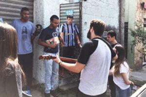 De mãos dadas, os Moços de Boa Vontade promovem momento de prece em frente à casa de morador do bairro da Casa Verde.
